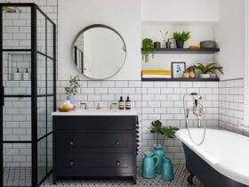 دستشویی با چیدمان تیره و وان در حمام و آیینه دایره