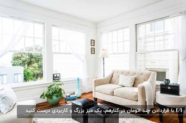 نشیمنی با پنجره های مربع بزرگ، مبلمان کرم و دو پاف مشکی به عنوان میز عسلی