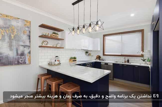 آشپزخانه با کابینت های سرمه ای، رویه کابینتی سفید چهارپایه هایی به رنگ مسی