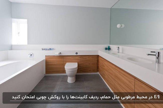 سرویس بهداشتی بزرگ و روشنی که دیوار مقابل وان با ردیف کابینت چوبی روشویی پوشانده شده