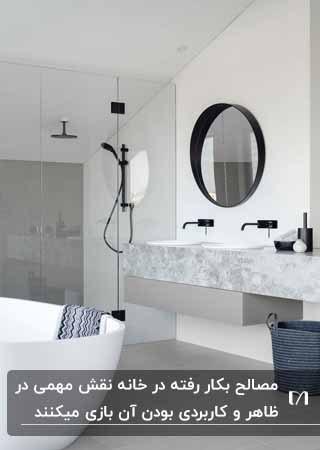 تصویر یک سرویس بهداشتی با استفاده از رنگ های سفید و مشکی و طوسی با آینه گرد و شیرآلات مشکی