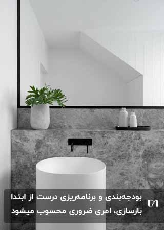 تصویر یک سرویس بهداشتی با دیوار بتنی، روشویی گرد سفید و شیرمشکی و گلدان بتنی