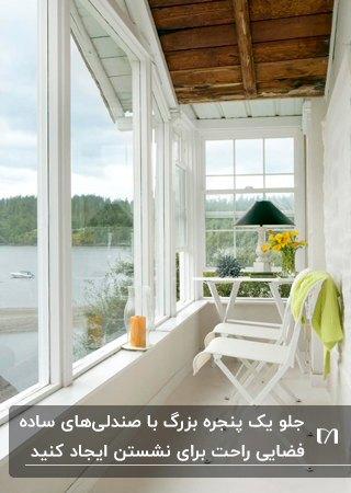 اتاق آفتابگیر باریک و کوچکی با میز و صندلی های سفید ، آباژور مشکی و گلدان گل