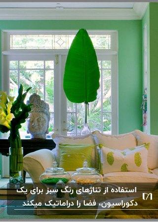 نشیمنی با مبلمان سفید، دیوارهای سبز، یک برگ آویز سبز و کوسن های طرحدار