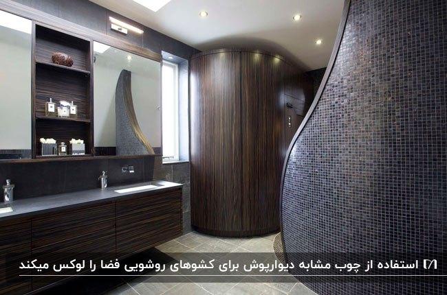 تصویر یک سرویس بهداشتی تیره با ترکیبی از کاشی های خاکستری و پنل های چوبی قهوه ای