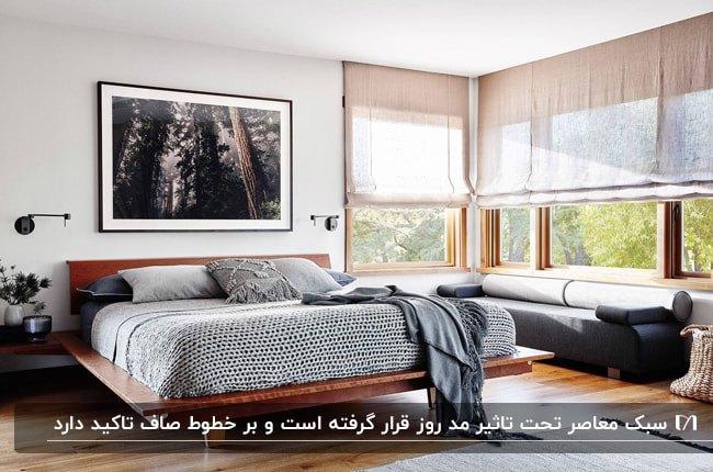 اتاق خواب معاصری با تخت خواب چوبی، تابلوی نقاشی بالای تخت و کاناپه خاکستری زیر پنجره