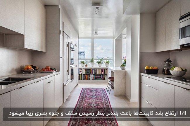 آشپزخانه ای با سقف کم ارتفاع و کابینت های کرم رنگی که تا سقف ادامه دارند