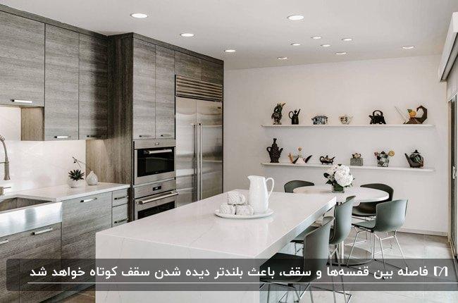 آشپزخانه ای با سقف کم ارتفاع، کابینت چوبی، کانتر سفید و قفسه های سفید افقی روی دیوار