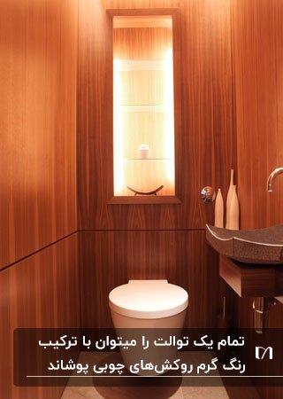تصویر یک توالت شیک با دیوارپوش چوبی و یک تاقچه تزئینی داخل دیوار