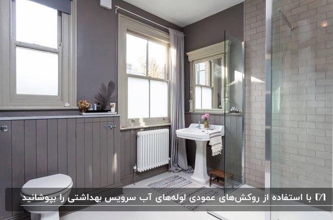 حمام و سرویس بهداشتی طوسی رنگی با پنل های عمودی دیوار و پنجره های مربعی