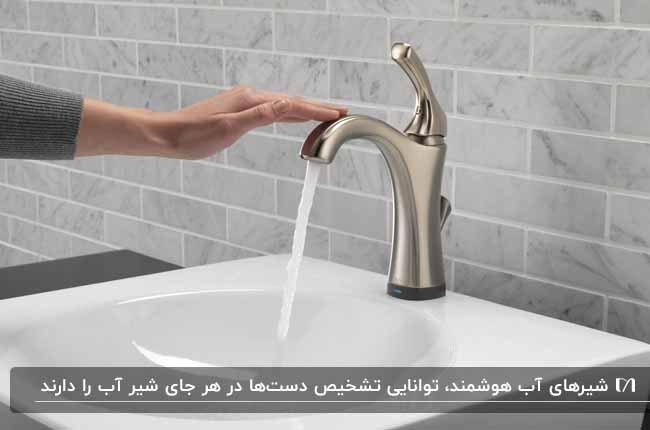 تصویر یک روشویی شرامیکی سفید به همراه شیر آب استیل هوشمند