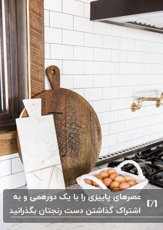 کانتر سفید با یک تخته چوبی گرد و یک تخته سفید مستطیلی و یک سبد تخم مرغ محلی