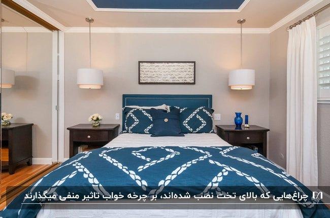 اتاق خوابی با تخت دو نفره و روتختی سفید و آبی و دو چراغ آویز سفید دو طرف تخت
