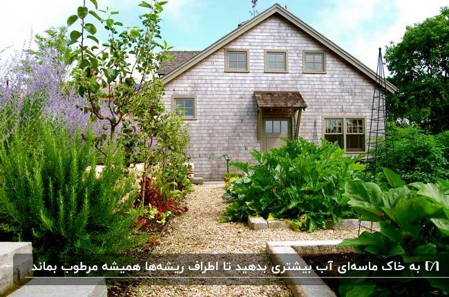 تصویر محوطه سازی و باغچه های ویلای آجری طوسی با درختان، گلها و گیاهان کاشته شده