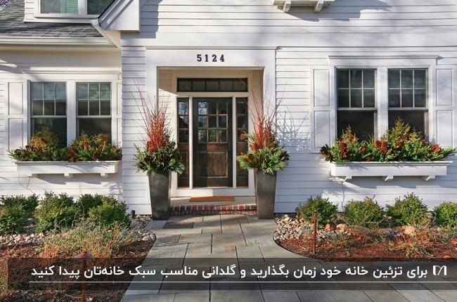 نمای ورودی خانه ای با باکس های گل دو طرف در ورودی و زیر پنجره