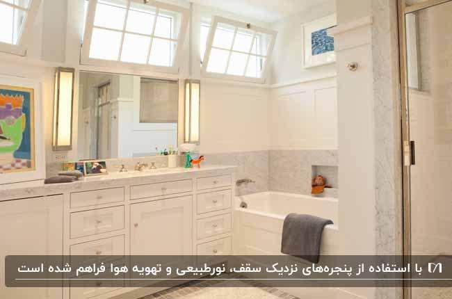 حمام سفید با وان و روشویی کابینتی و پنجره هایی نزدیک سقف