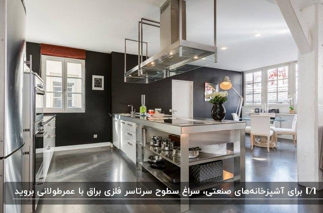 تصویر یک آشپزخانه صنعتی براق با کابینت و لوازم استیل