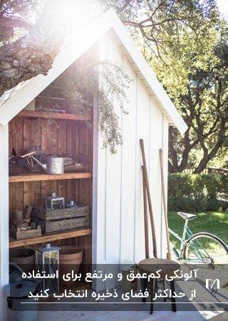 آلونک باغبانی چوبی سفیدی که داخلa قفسه بندی های چوبی است