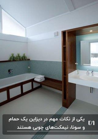 سرویس بهداشتی با کاشی های نصفه آبی روی دیوار و نیمکت و قفسه های دور روشویی چوبی