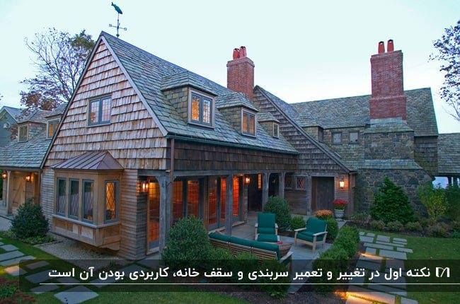 خانه ای با نمای تخته های چوبی و سقف شیروانی به همراه مبلمانی با پارچه سبز در حیاط
