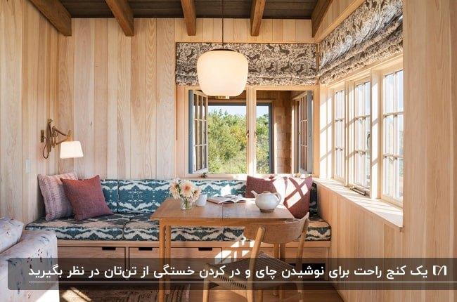 گوشه دنج یک کلبه چوبی با میزو صندلی و نیمکت چوبی زیر پنجره