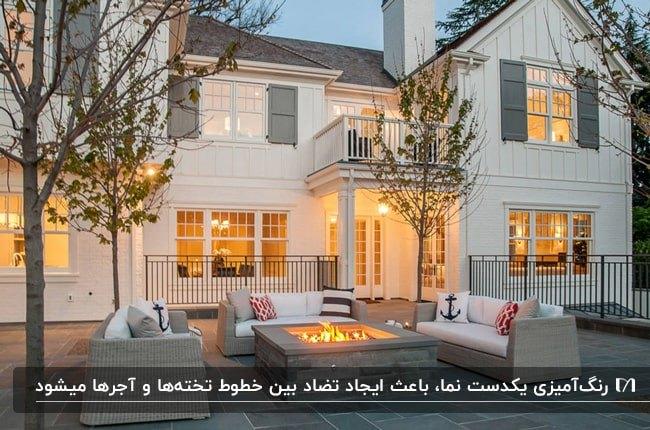 نمای سفید خانه ای با تخته های بزرگ و کوچک به همراه آجر سفید و مبلمان و گودال اتش در محوطه حیاط