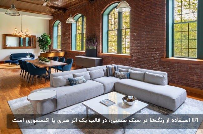 خانه ای صنعتی با دیوارهای آجری، مبل ال شکل طوسی، میز غذاخوری چوبی با صندلی های سورمه ای