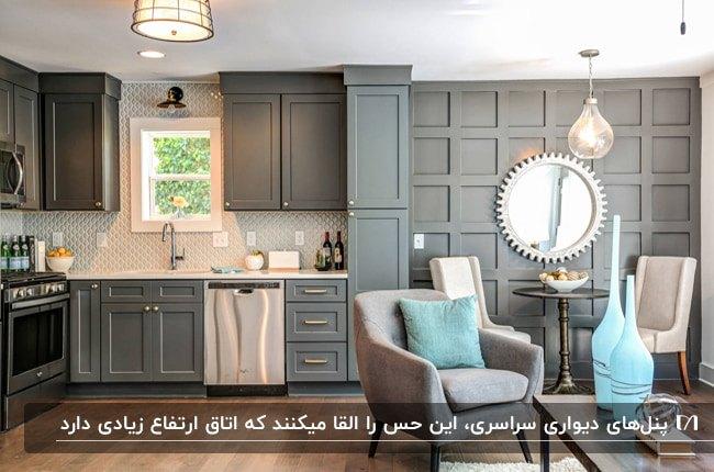 آشپزخانه ای کنار اتاق غذاخوری با سقف کم ارتفاع به همراه پنل دیواری مربع و کابینت همرنگ