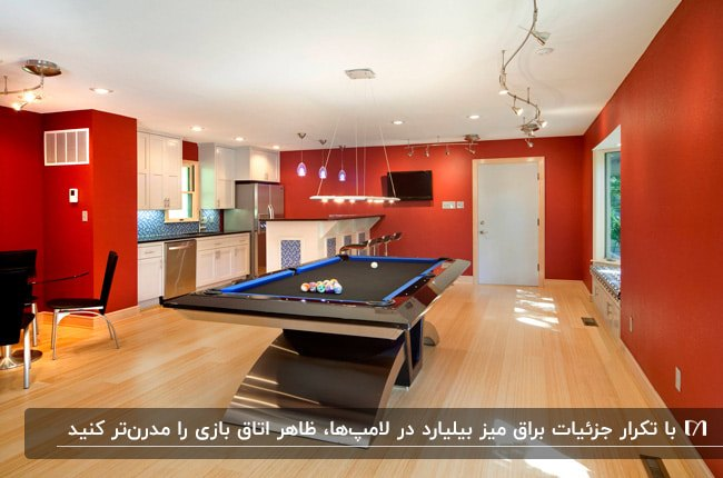 اتاق بازی بزرگی با دیوارهای قرمز رنگ و یک میز بیلیارد فلزی براق با چراغ های آویز بالای میز