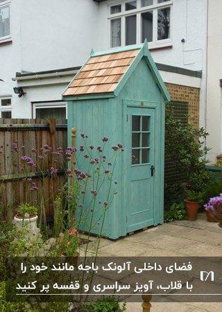تصویر یک آلونک باغبانی چوبی به رنگ سبز شبیه باجه تلفن