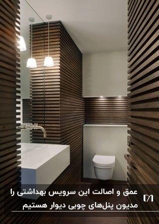 یک سرویس بهداشتی مدرن با دیوارپوش های چوبی افقی و لوستر آویز برای روشنایی