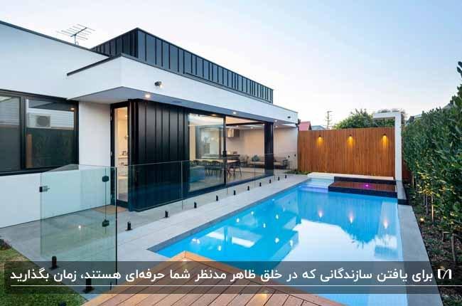 خانه ای مدرن با نمای سفید و مشکی و استخر در حیاط و دیوارپوش های چوبی