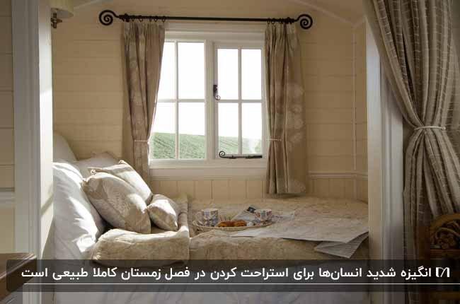 گوشه دنج زیر پنجره به همراه تخت و کوسن و بالش برای خواب زمستانی