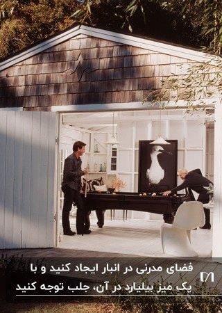 تصویر یک میز بیلیارد چوبی مشکی در انباری سفیدی که به اتاق بازی تبدیل شده است