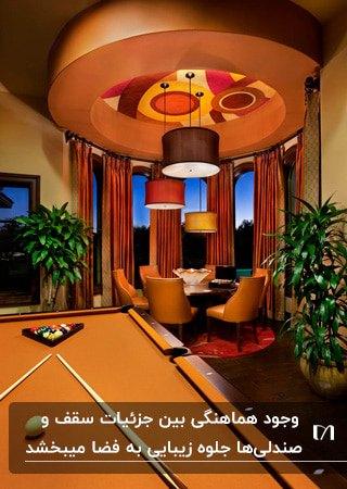 اتاق بازی با تم قرمز و نارنجی، میز بیلیارد، میز غذاخوری گرد و صندلی هایش با سقف کاذب طراحی شده