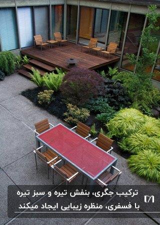 حیاطی با میز و صندلی های چوبی و فلزی به همراه گیاهان بنفش و جگری و سبز و فسفری