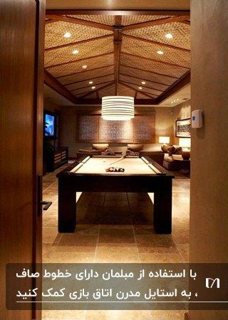 اتاق بازی مدرنی با رنگ های کرم و قهوه ای و یک میز بیلیارد مستطیلی وسط اتاق