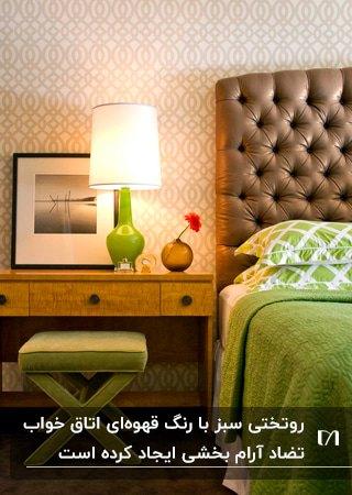 اتاق خوابی با روتختی، چهارپایه و چراغ سبز رنگی کنار تخت قهوه ای
