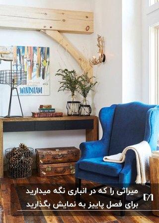 گوشه ای دنج با لوازم قدیمی چوبی و یک مبل تک نفره آبی کلاسیک