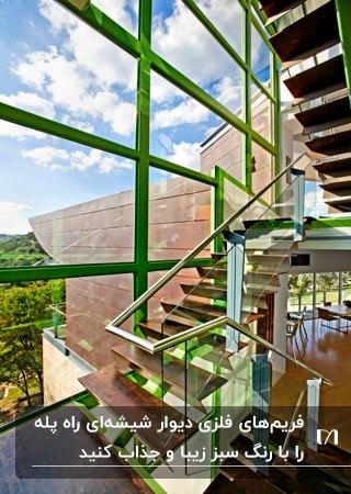 راه پله ای با پله های چوبی، حفاظ شیشه ای و فریم فلزی سبز رنگ دیوار شیشه ای با منظره عالی
