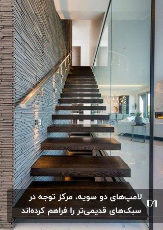 نورپردازی راه پله ای چوبی با چراغ های دو سویه روی دیوارپوش سنگی