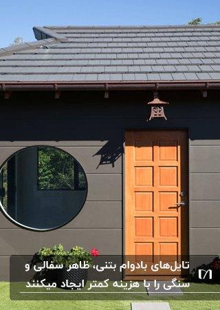 نمای خاکستری خانه ای با پنجره گرد، درب مشبک نارنجی و سقف بتنی