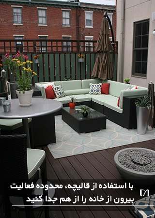 پاسیویی با مبلمان ال شکل سبز کمرنگ و کوسن های قرمز به همراه یک فرش ساده