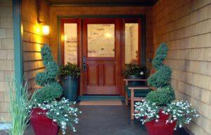 تصویری از ورودی یک خانه که با گلدان های گل طبیعی تزئین شده است