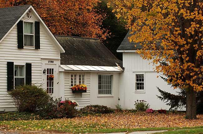 خانه ای ویلایی سفید در فصل پاییز با برگ های زرد