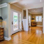 تصویری از یک ورودی داخلی روشن و زیبا با در شیشه ای و کف چوبی
