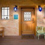 تصویر یک ورودی سنتی آجری با درب و نیمکت چوبی
