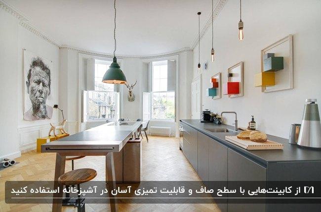 کابینت های صاف و صیقلی خاکستری و میز غذاخوری چوبی به عنوان جزیره