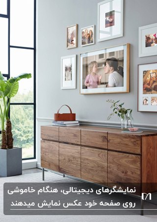کنسول چوبی و تعدادی قاب عکس و یک نمایشگر دیجیتال روی دیوار خانه