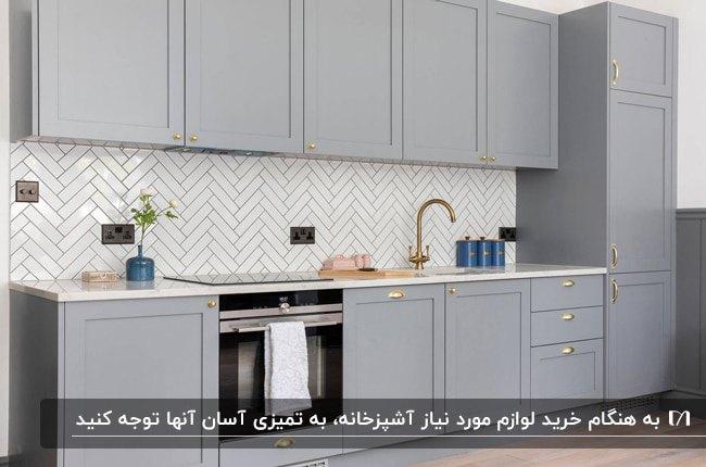 آشپزخانه ای با کابینت های طوسی و شیرآلات طلایی با کاشی های بین کابینتی طرحدار